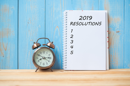 Foto de 2019 Resolutions text on notebook and retro alarm clock  on table and copy space. Goals, Mission and New Start Concept - Imagen libre de derechos