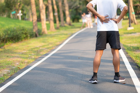 Foto de Young fitness man holding his sports leg injury. muscle painful during training. Asian runner having back ache and problem after running and exercise outside morning. sport and healthy concepts - Imagen libre de derechos