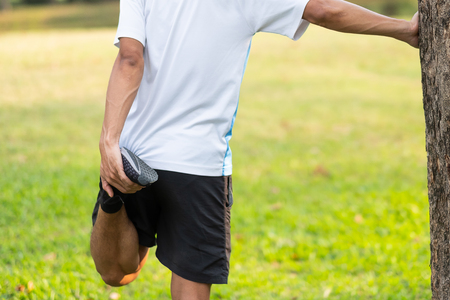 Photo pour Young athlete man streching in the park outdoor. male runner warm up ready for jogging on the road outside. asian Fitness walking and exercise on footpath in morning. wellness and sport concepts - image libre de droit