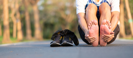 Foto de Young fitness man holding his sports leg injury. muscle painful during training. Asian runner having feet sole ache and problem after running and exercise outside morning. sport and healthy concepts - Imagen libre de derechos