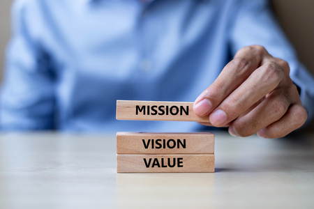 Foto de Businessman hand holding wooden building blocks with MISSION, VISION, CORE VALUE Concepts - Imagen libre de derechos