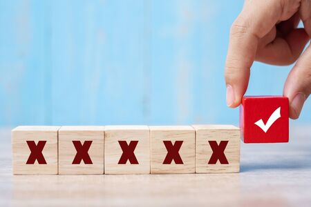Photo pour business man holding Wood cubes block with Right symbol different from Wrong symbol on table background - image libre de droit