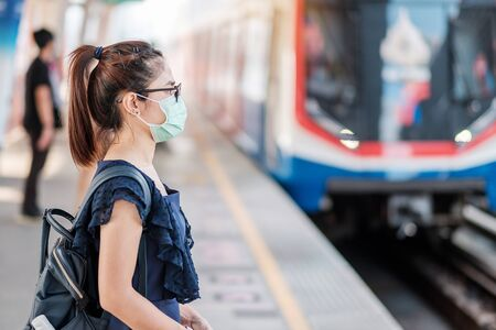 Photo for young Asian woman wearing Surgical face mask against Novel coronavirus or Corona Virus Disease (Covid-19) at public train station. Hygiene, Healthcare and infection concept - Royalty Free Image