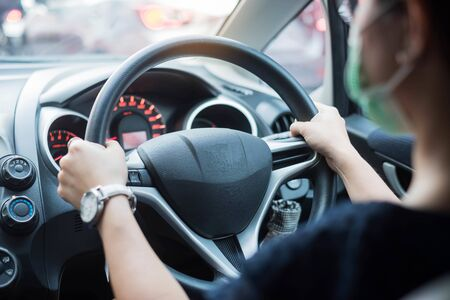 Photo pour Young woman wearing protective face mask and hand controlling steering wheel in her car, against coronavirus or Corona Virus Disease (Covid-19). personal Hygiene lifestyle and New Normal concept - image libre de droit