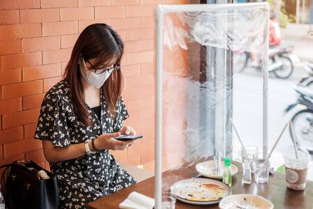 Photo pour Asian woman using smartphone during dining time in restaurant with separated of shield plastic partition, protect coronavirus inflection. social distancing, new normal and life after covid-19 pandemic - image libre de droit