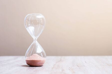 Photo pour Hourglass on table, Sand flowing through the bulb of Sandglass measuring the passing time. countdown, deadline, Life time and Retirement concept - image libre de droit