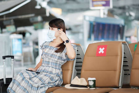 Photo pour Young female wearing face mask and using mobile smartphone in airport, protection Coronavirus disease (Covid-19) infection, Asian woman traveler sitting on chair. New Normal and social distancing - image libre de droit