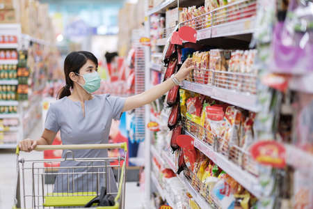 Foto für Young woman wearing protective face mask and  shopping in grocery or department store protect coronavirus inflection. social distancing, new normal and life under covid-19 pandemic - Lizenzfreies Bild
