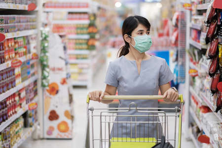 Photo pour Young woman wearing protective face mask and  shopping in grocery or department store protect coronavirus inflection. social distancing, new normal and life under covid-19 pandemic - image libre de droit