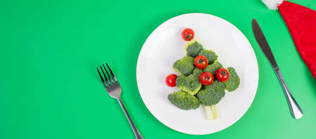 Christmas tree of organic vegetables on white plate; Broccolis and tomatoes with fork and knife on green background. Merry Xmas and happy New Year party, New You, Healthy food and vegetarian concept