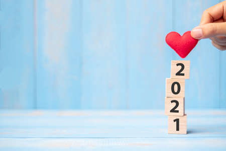 Photo for Business man hand holding red heart shape over 2021 wooden cubes on blue table background with copy space for text. Business, Resolution, New Year New You and Happy Valentine's day holiday concept - Royalty Free Image
