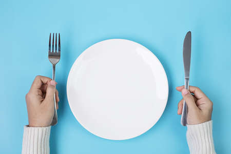 Photo pour Hands holding knife and fork above white plate on blue background., dieting, weight loss, dining and kitchenware concept - image libre de droit