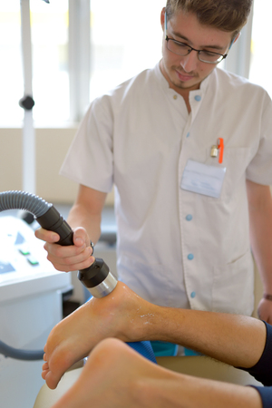 Photo for Physiotherapist performs ultrasound physical therapy treatment - Royalty Free Image