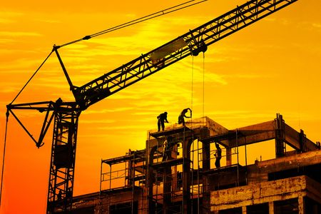Worker on roof and crane on construction site silhouetted against orange sunset