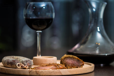 Meat fillet and sausage eith red wine on cutting wooden plateau