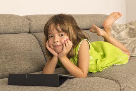 Little girl playing with a digital tablet at home on a sofa with her legs crossed