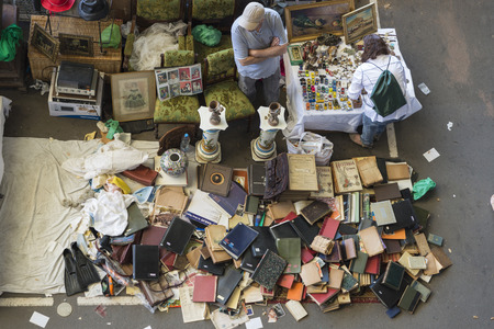 Barcelona, Spain - June 18, 2014   Seller at his post of objects and furniture resale while a client is looking for something to buy in the most famous flea market in Barcelona, also known as Els Encants or Els Encants Vells, located in Glories neighborho