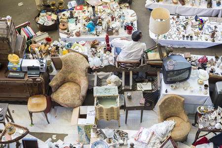 Barcelona, Spain - June 18, 2014   Seller at his post of objects and furniture resale in the most famous flea market in Barcelona, also known as Els Encants or Els Encants Vells, located in Glories neighborhood  Seller at his post of objects and furniture