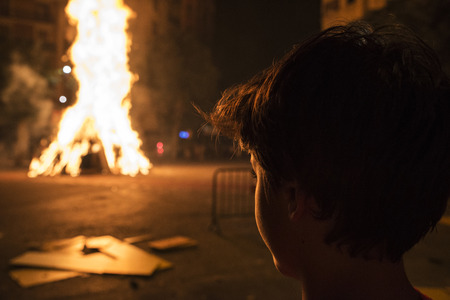 Boy looking at a bonfire at night to celebrate the festivity of Sant Joan on a street in Barcelona, Catalonia, Spain