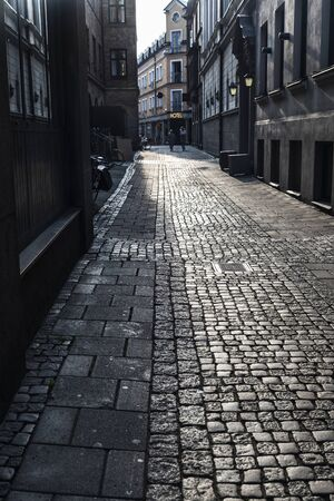Photo pour Paved street with a sign hotel at sunset in the old town of Malmö with people around in Sweden - image libre de droit