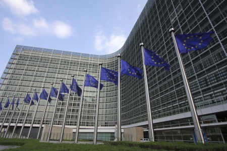 European flags waving in the wind, before the European Commission Berlaymont building in Brussels, Belgium