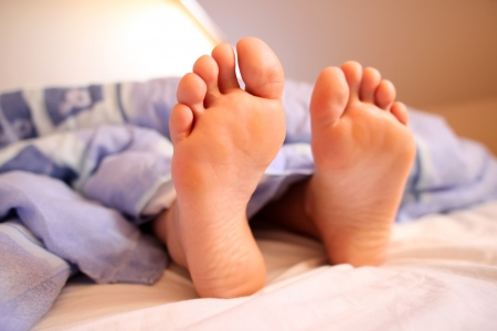 Young woman s bare feet in bed