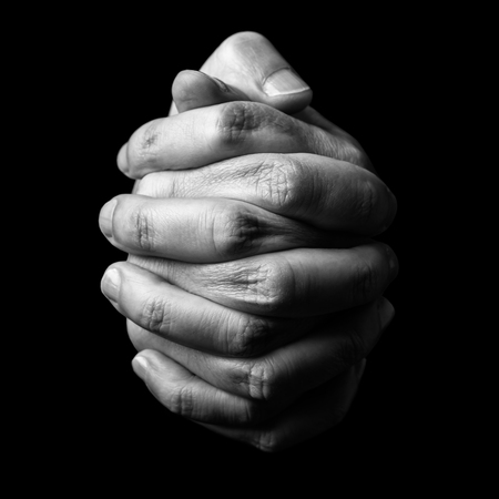 Photo pour Low key, close up of hands of a faithful mature man praying, hands folded, interlaced fingers in worship to god. Isolated black background. Concept for religion, faith, prayer and spirituality. - image libre de droit