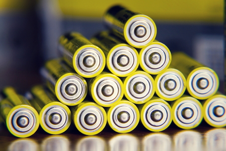 Stack of yellow AA batteries close up abstract color background
