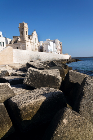 Seafront with catholic Church Chiesa San Salvatore in Monopoli, Adriatic sea, Italy, sunny summer day