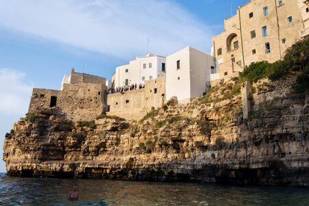 POLIGNANO A MARE, ITALY - JULY 6 2018: Tourist looking from view in historic center to lovely beach Lama Monachile, Adriatic Sea, Apulia, Bari province on July 6, 2018 in Polignano a Mare, Italy.