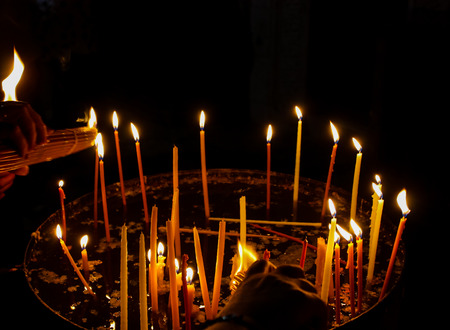 Lighting candles in the Church of the Holy Sepulchre in the Old City of Jerusalem