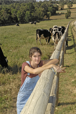 portrait of a farmer with her cows in the field