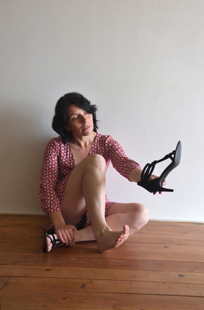 Foto de barefoot woman with a shoe in her hand - Imagen libre de derechos