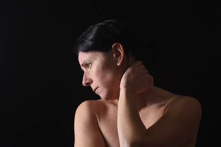 Photo pour middle-aged woman with pain in the neck on black background - image libre de droit