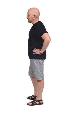 Photo pour bald man in profile with shirt shorts and sandals, hand on hip - image libre de droit