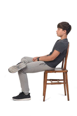 Photo pour side view of teenage boy sitting on a chair with white background, looking to the side and relaxed - image libre de droit