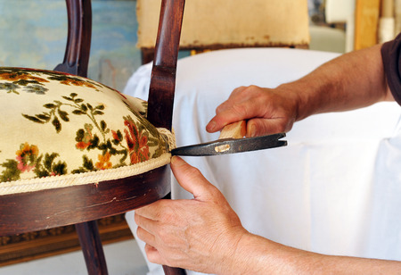 Photo pour Traditional upholsterer changing the seat upholstery of a chair - image libre de droit