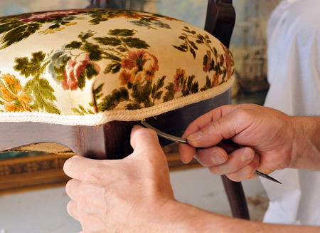 Photo pour Traditional upholsterer finishing work, changing the upholstery of an antique chair seat - image libre de droit