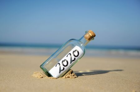 Photo pour Happy New Year 2020, message in a bottle on the sand of beach. Summer vacation concept - image libre de droit