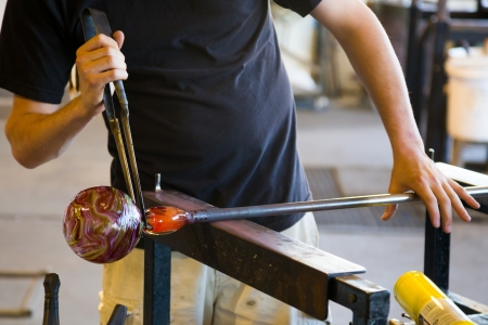 A man takes motlen glass and shapes it using some specialized tools for glassblowing art.