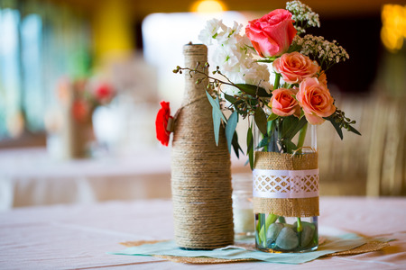 Photo pour DIY wedding decor table centerpieces with wine bottles wrapped in burlap twine and rose flowers. - image libre de droit