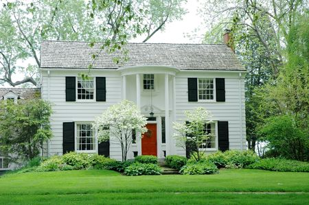White formal house with siding, black shutters and bright green, manicured lawn / garden