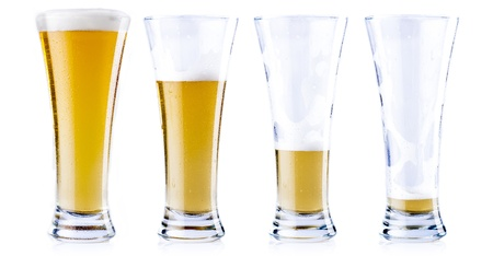 Four glasses of beer in various stages, from full to empty