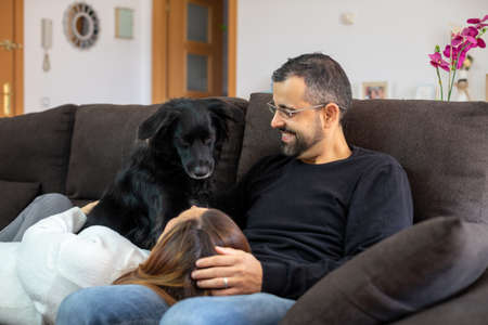 Foto de Young happy couple on the sofa at home with their black dog. Woman resting her head on the legs of her partner. - Imagen libre de derechos