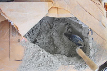Foto de close up trowel in a bag of cement powder - Imagen libre de derechos