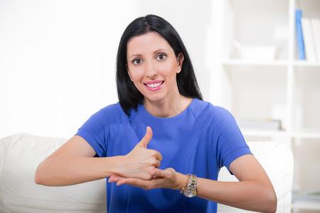 Photo pour Beautiful smiling deaf woman using sign language - image libre de droit