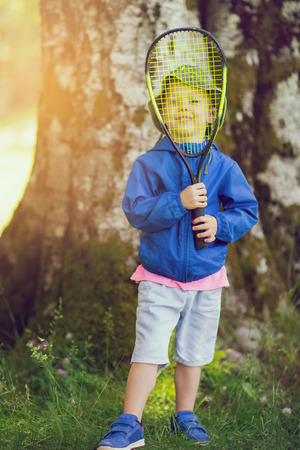 Little boy playing tennis at park