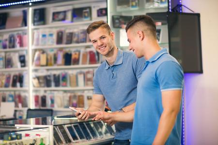Foto de Two young men choosing smart phone in the store smiling - Imagen libre de derechos