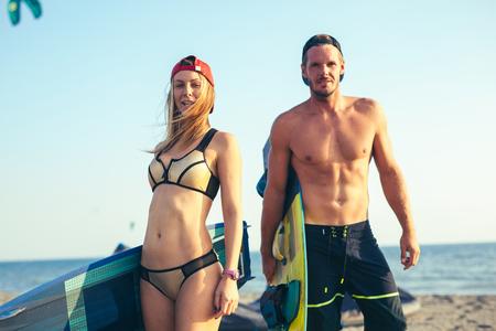 Photo pour Pretty smiling Caucasian woman kitesurfer enjoying summertime on sandy beach with her boyfriend. - image libre de droit