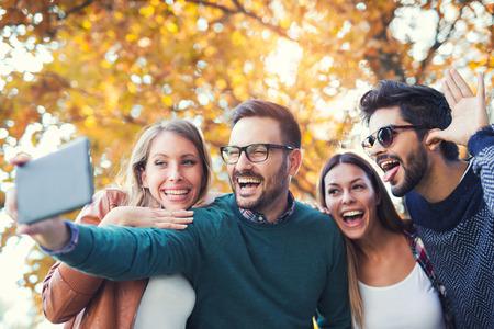 Photo pour Group of four funny friends taking selfie with a smart phone in park - image libre de droit